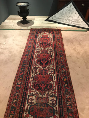 A red ground wool Persian runner rug- 295cm x 95cm
