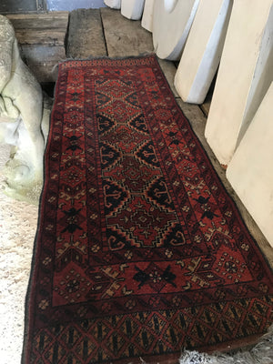 A short red ground Persian runner rug