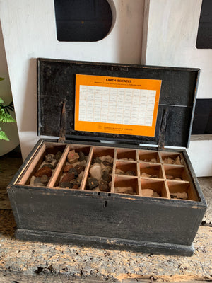 A large geological rock specimen collection in a wooden box