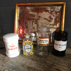 A large glass apothecary jar with hand painted gold leaf label