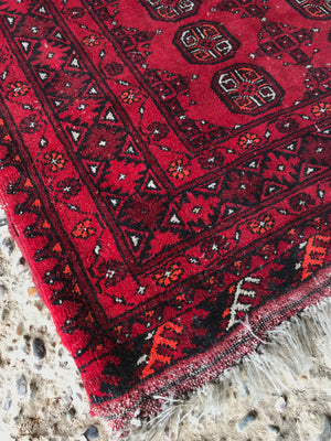 A large rectangular red Persian hand knotted wool carpet 157cm X 107cm