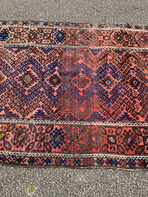 A large rectangular red brown ground Persian rug