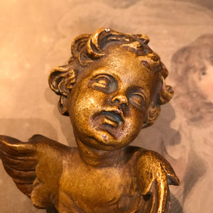 A pair of ceramic wall hanging winged putti busts