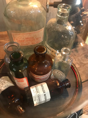 A collection of apothecary bottles and jars under a glass dome