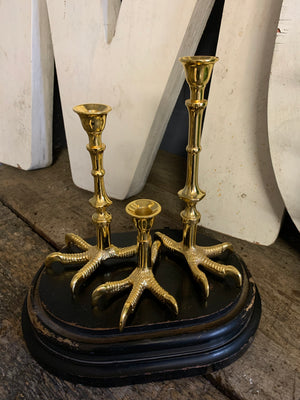 A trio of graduated gold claw candlesticks