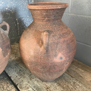 A pair of large terracotta urns with double lug handles