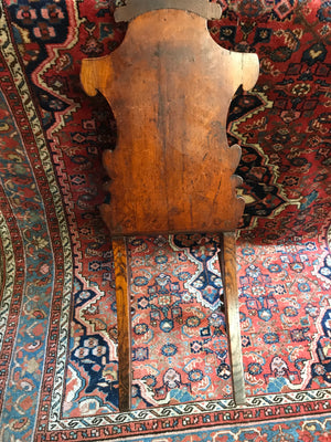 A 19th Century carved wood hall chair with monogrammed armorial crest
