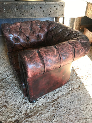 An oxblood Chesterfield armchair with button back and seat