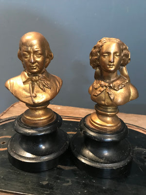 A pair of gilt spelter Gentleman and Lady busts on ebonised bases