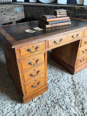 A green leather topped oak pedestal desk with brass handles