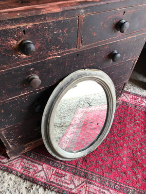 A distressed oval gilt wall mirror