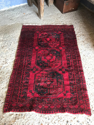 A Persian red ground lozenge rectangular rug