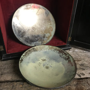 A pair of distressed parabolic mirrors