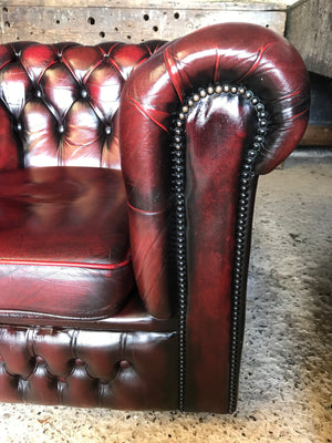 An oxblood red Chesterfield armchair with button back