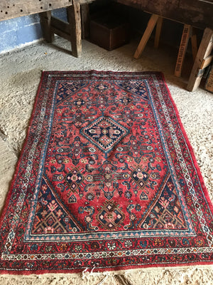 A rectangular red ground wool Persian rug