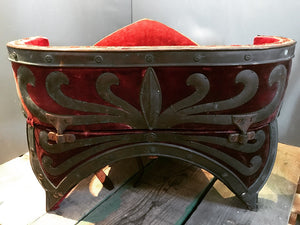A red velvet and worked metal horse saddle