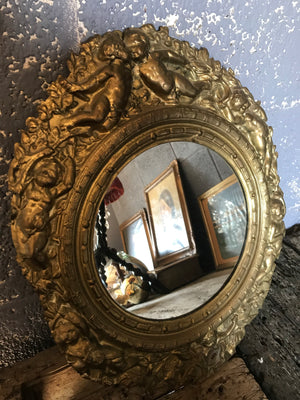 A pair of 19th Century brass repoussé mirrors with cherub detailing