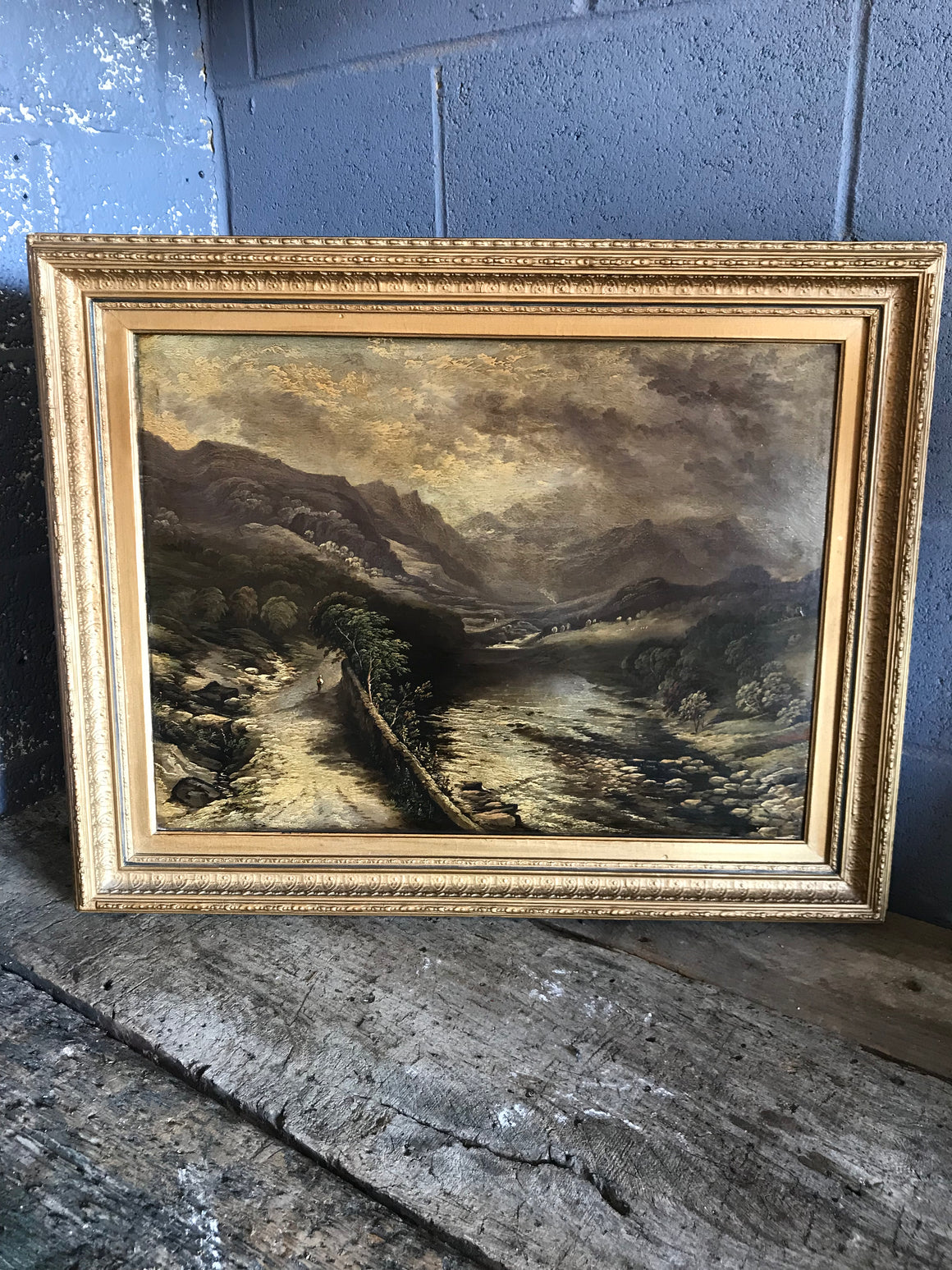 A 19th Century landscape oil painting depicting a mountain and river setting