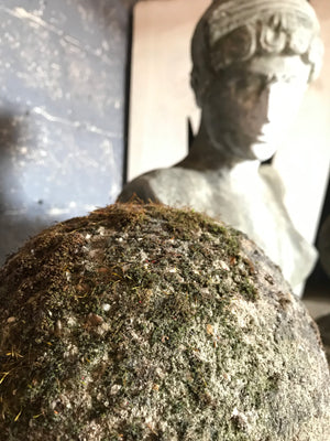 A pair of mossy stone ball pillar caps