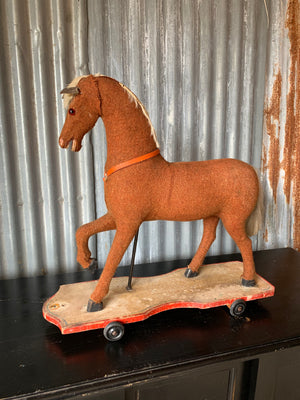 A large pull along rocking horse on wheels