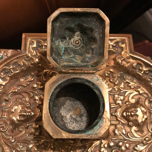 A rococo brass cherub and lion head inkwell and pen tray