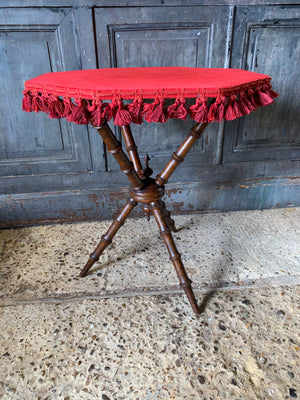 An octagonal red velvet faux bamboo gypsy table
