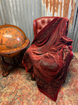 A large worn red velvet throw