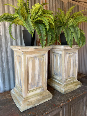 A pair of white pedestal stands