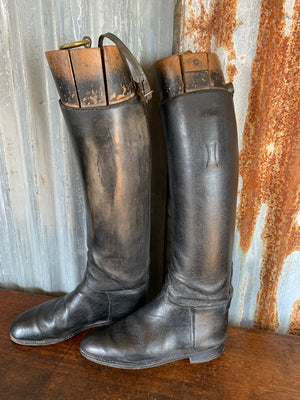 A pair of black leather riding boots with wooden lasts