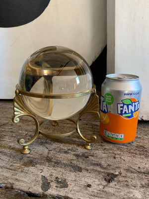 A large fortune teller's crystal ball on a brass tripod base