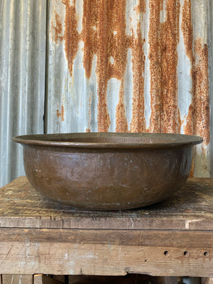 A very large hand beaten copper bowl