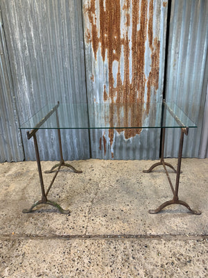 A cast iron trestle base dining table with glass top