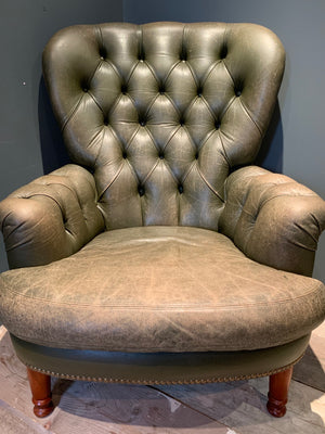 A small green leather Chesterfield armchair