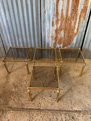 A set of four metamorphic square Hollywood Regency stacking side tables with smoked glass