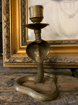 A pair of Indian or North African brass cobra candlesticks
