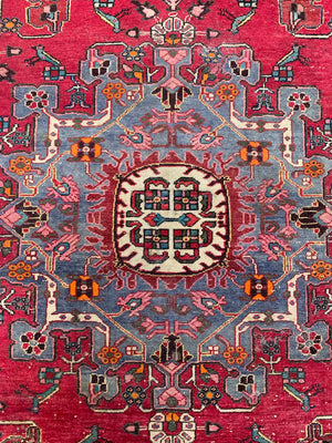 A large hand woven Persian red ground rectangular rug with bird motifs
