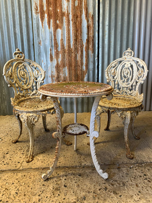 A pair of white cast iron Coalbrookedale chairs and complimentary bistro table