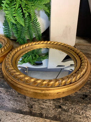 A pair of large gold convex mirrors with rope twist detailing