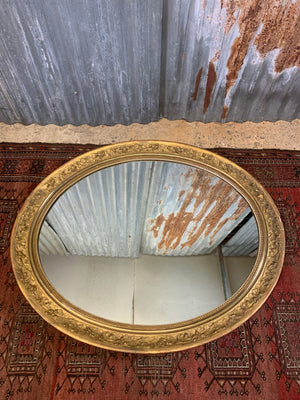 A large 19th century oval gilt mirror