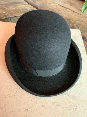 A vintage black bowler hat, bow tie and white gloves