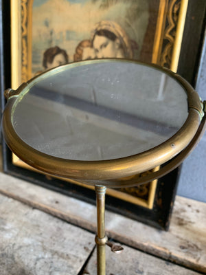 An adjustable brass grooming mirror
