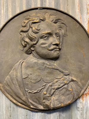 A metal roundel relief plaque of a gentleman