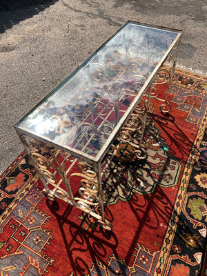 A weathered white wrought iron console table with glass top