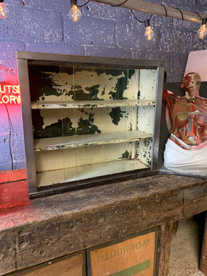 A vintage industrial stripped steel medical cabinet