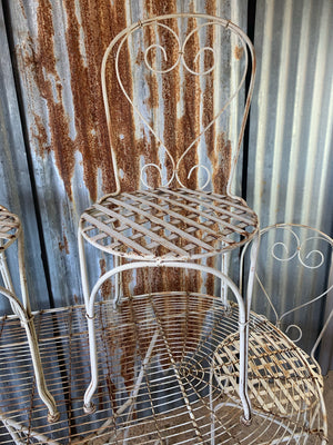 A white French wirework garden table and four chairs