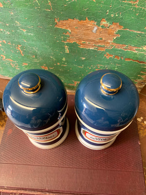 A pair of blue porcelain apothecary jars with gold glass labels