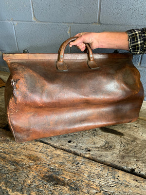 A large brown leather monogrammed Gladstone bag