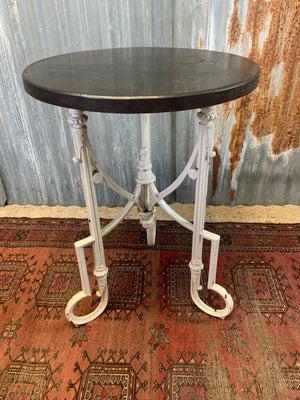 A white cast iron bistro garden table with wooden top