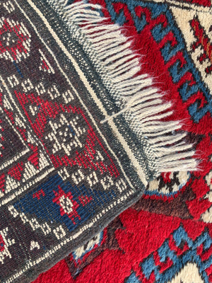 A long red ground Persian runner rug