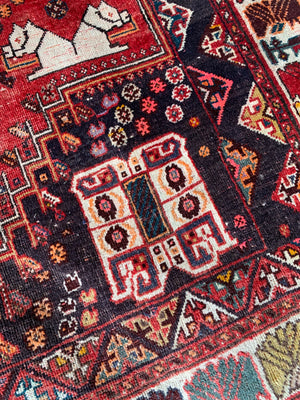 A large red ground rectangular Persian rug with camel motif